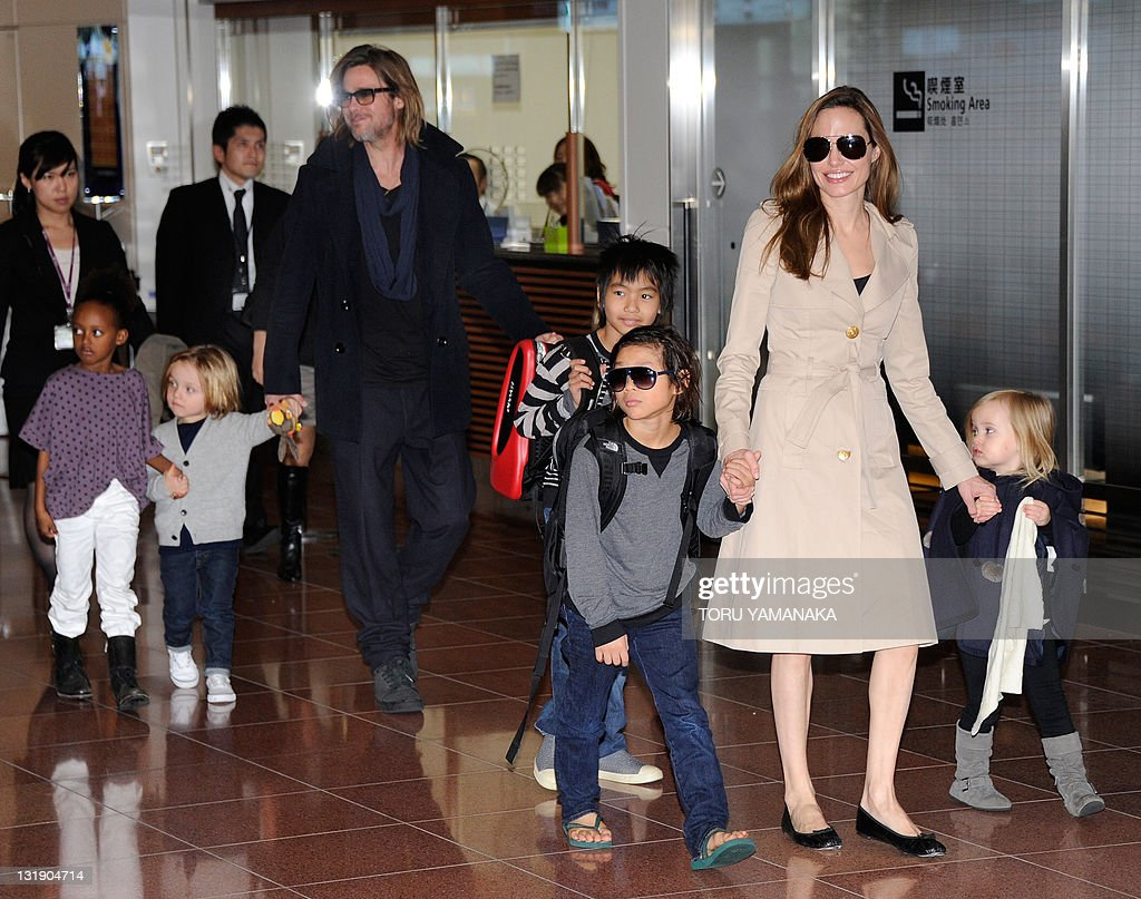Accompanied by their children, US movie stars Brad Pitt and Angellina Jolie appear before photographers upon their arrival at Haneda Airport in Tokyo on November 8, 2011. Brad Pitt is here for the Japan premiere of his last film 'Moneyball'. AFP PHOTO/Toru YAMANAKA