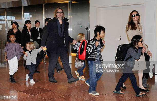 Accompanied by their six children US movie star Brad Pitt and Angellina Jolie appear before photographers upon their arrival at Haneda Airport in...