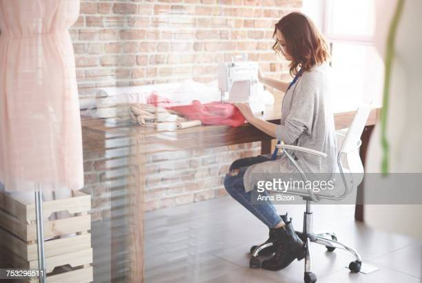 accomplished female tailor busy sewing. debica, poland - stiches stock photos and pictures