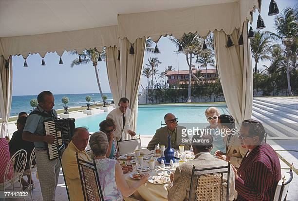 Accordion music accompanies a meal by the pool at the home of Molly Wilmot in Palm Beach Florida April 1968