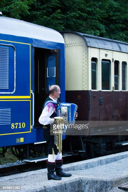 accordion player in traditional costume entertains travellers beside locomotive in station lake bled slovenia - accordionist stock pictures, royalty-free photos & images