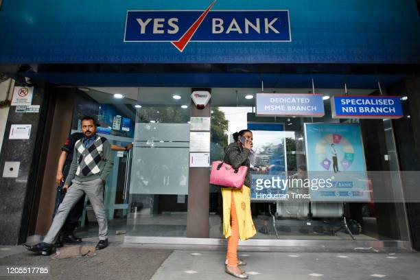 Account holders are seen outside the Yes Bank branch office at Janpath, in New Delhi, India, on Friday, March 6, 2020.