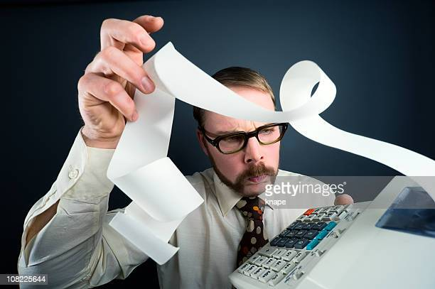 accountant adding numbers on calculator - economist stock pictures, royalty-free photos & images