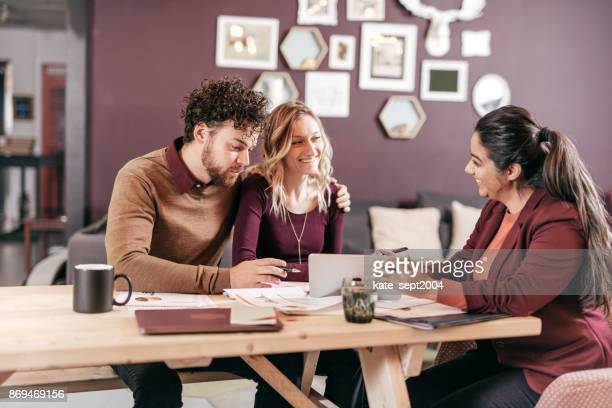 accountant explaining taxes for couple - borrowing stock pictures, royalty-free photos & images