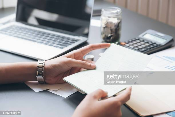 accountant hands holding saving account passbook, book bank. - wages stock pictures, royalty-free photos & images
