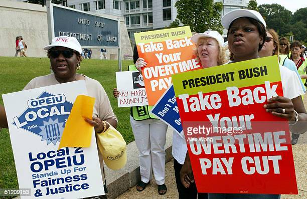 Accounting clerk Fronnie Barlow of American Federation of Government Employees holds a poster as she demonstrates with coworkers Tonya Kelly an...