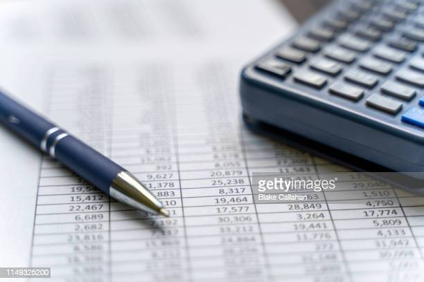 accounting table with pen and calculator - politics stock pictures, royalty-free photos & images
