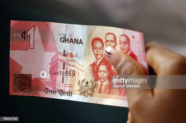 A woman holds 03 July 2007 in Accra a bill of new currency the new cedi that Ghana put in circulation that day although the old money will still be...