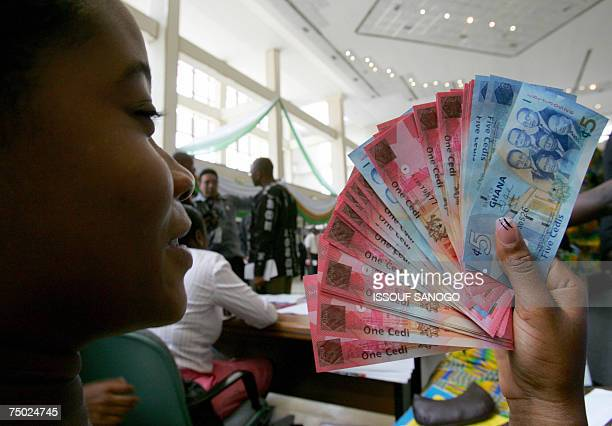 A woman holds 03 July 2007 in Accra a wad new currency the new cedi that Ghana put in circulation that day although the old money will still be valid...