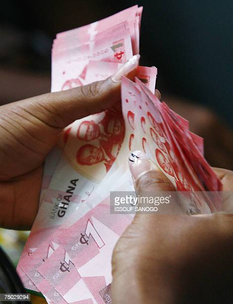 A woman holds 03 July 2007 in Accra a wad of new currency the new cedi that Ghana put in circulation that day although the old money will still be...