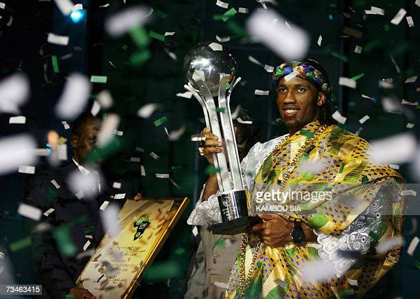Chelsea and Ivory Coast striker Didier Drogba poses with his trophy next to the president of the Confederation of African Football Issa Ayatou after...