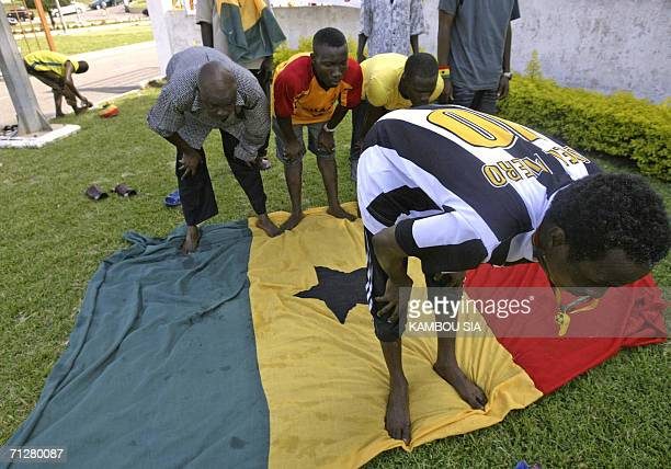 Ghanaian football supporters pray 22 June 2006 on a national flag in Accra before Ghana's Black Stars match against the United States in Cologne...