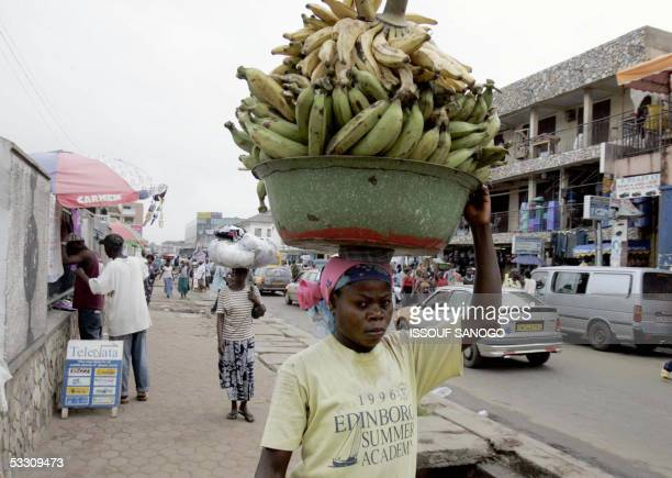 With ' Ghana girl porters carry heavy burden of forced labor and forced sex' A young Ghanian girl works 19 June 2005 in a street of Accra Ajara...