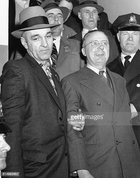 """Accused """"Mad Bomber"""" Booked. Waterbury, Conn.: Flashing a hearty smile, 53-year-old George Metesky is surrounded by police as he is booked at the..."""
