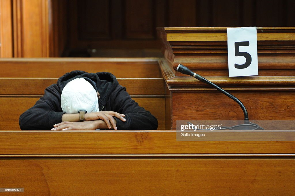 Accused murderer Xolile Mngeni rests his head in the Cape Town High Court on November 26, 2012 in Cape Town, South Africa. Mngeni was found guilty of robbery with aggravating circumstances, premeditated murder and illegal possession of a firearm and ammunition, after his involvement with the murder of Anni Dewani.