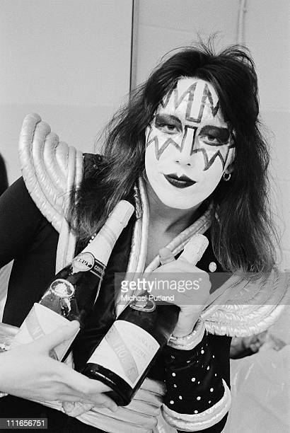 Ace Frehley of Kiss portrait backstage in dressing room in stage make up holding bottle of champagne New York February 1977