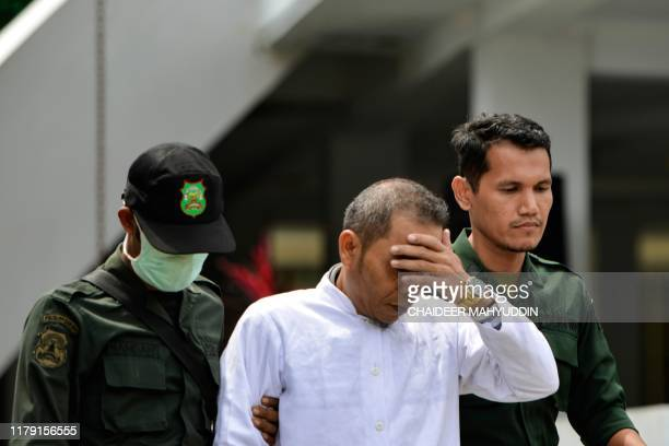 Aceh Ulema Council member Mukhlis is escorted by members of the Sharia police before being whipped in public in Banda Aceh on October 31 2019 An...