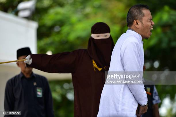 Aceh Ulema Council member Mukhlis reacts as he is whipped in public by a member of the Sharia police in Banda Aceh on October 31, 2019. - An...