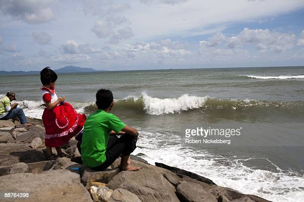 Acehnese children sit and watch waves on a newly constructed jetty in Aceh province's capital city June 15 2009 in Banda Indonesia Following the...