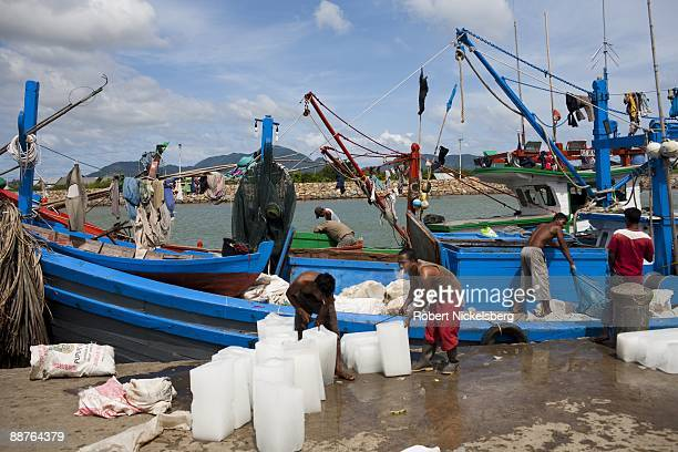 Acehnese fishermen load their boat with ice blocks at the newly constructed port before heading out to sea in Aceh province's capital city June 15...