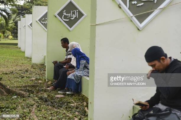 Acehnese gather to remember loved ones at a mass graves site in Banda Aceh on December 26 who perished in the tsunami which devastated Aceh province...