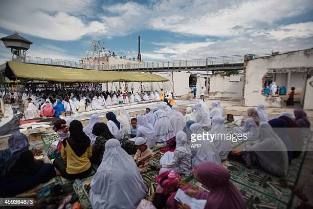 Acehnese people attend a mass prayer to mark the 9th anniversary of Asian tsunami disaster December 26 in Banda Aceh on December 26 2013 About one...