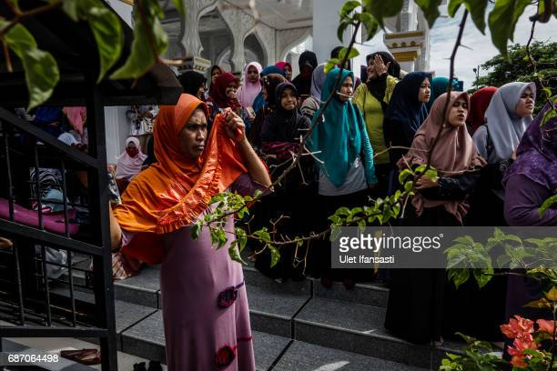 Acehnese people attend public caning for violations against Sharia law at Syuhada mosque on May 23 2017 in Banda Aceh Indonesia The two young gay men...