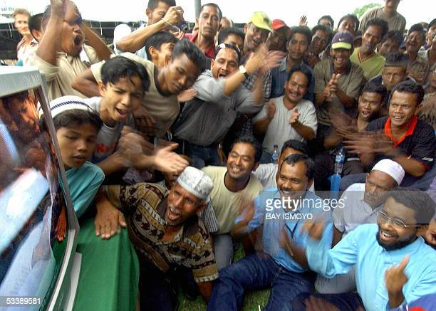 Acehnese people cheer as they watch the televised signing ceremony in Finland of a peace pact between the Indonesian government and Aceh separatist...