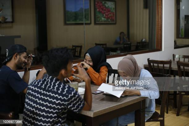 Acehnese people sit at a restaurant in Bireun a district in Indonesia's easternmost province Aceh on September 5 2018 A district in Indonesia's...