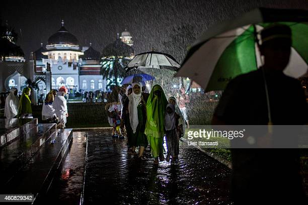 Acehnese people walk on the rain after they attend for an collective zikr to commemorate the ten anniversary of tsunami at Baiturrahman grand mosque...