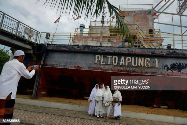 Acehnese pose for a photo next to a shipturnedinto a memorial which was pushed some 25 kilometres inland by the 2004 tsunami in Banda Aceh on...
