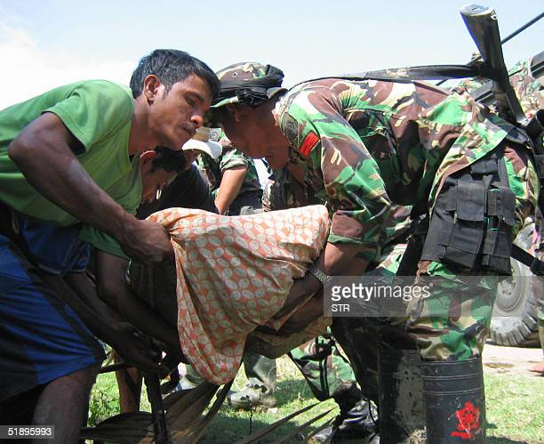 Acehnese residents and soldiers evacuate victims of tidal waves following a strong quake which hit Aceh province at Geulanggang Baroh Tanah Pasir...