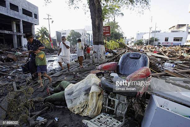 Acehnese walk amid dead bodies and debris thrown around by a Tsunami that hit the Indonesian City of Banda Aceh 150 miles from southern Asia's...