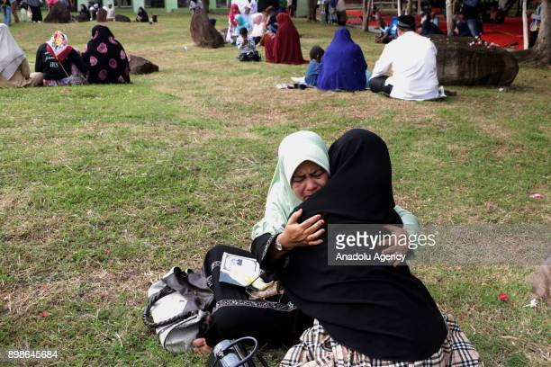 Acehnese women hug each other as people gather for the 13th anniversary of Tsunami commemoration at Ulee Lheue Banda Aceh in Aceh Indonesia on...