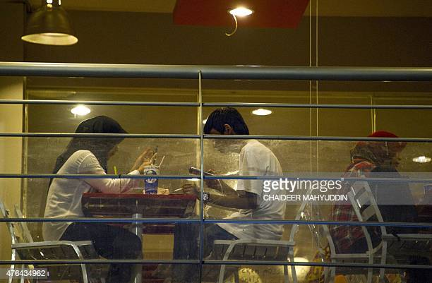 Acehnese women sit in a restaurant in Banda Aceh on June 9 2015 Women in the Indonesian city of Banda Aceh have been banned from venues like cafes...