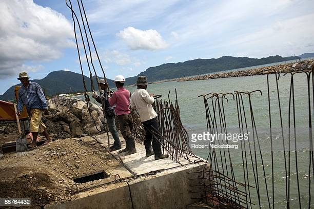 Acehnese workmen finish setting a concrete drain on a newly constructed jetty in Aceh province's capital city June 15 2009 Following the December 26...