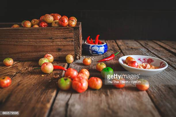 Acerolas And Chili Peppers On Wooden Table