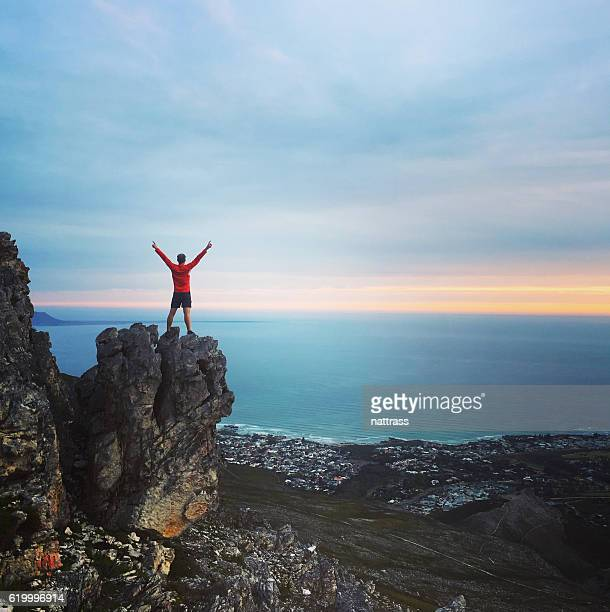 achievement - male standing on a mountain top - tall high stock photos and pictures