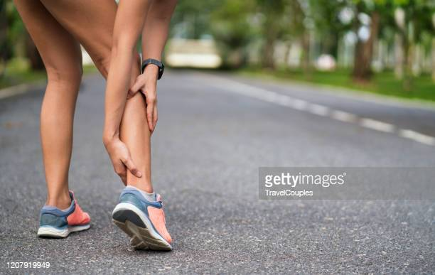 achilles injury on running outdoors. women holding achilles tendon by hands close-up and suffering with pain. ankle twist sprain accident in sport exercise running jogging. - muskel stock-fotos und bilder