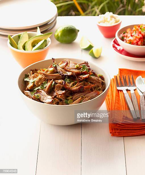 Achiote and orange pulled pork in bowl, close-up