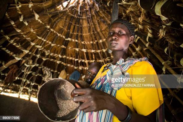 TOPSHOT Achol Ayut holds her malnourished child Nyibol Lual 25 years old and a pot with the only stock of sorghum for her five children on May 31 at...