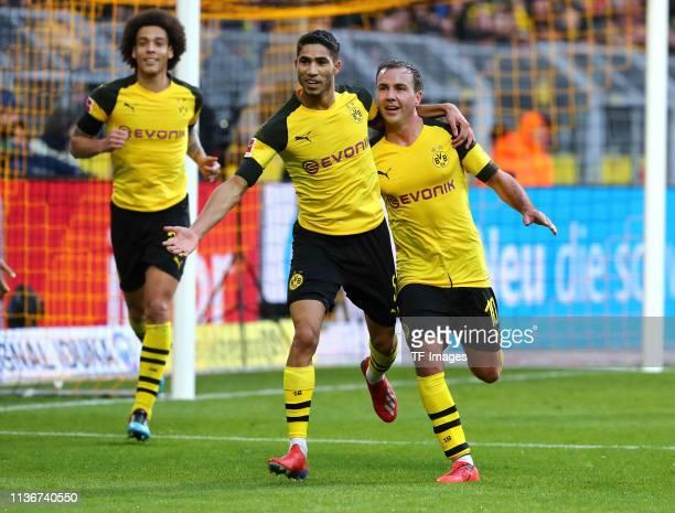 Achraf Hakimi of Borussia Dortmund celebrates after scoring his team's second goal with Mario Goetze of Borussia Dortmund and Axel Witsel of Borussia...