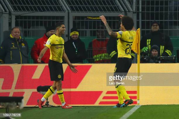 Achraf Hakimi of Borussia Dortmund celebrates with teammate Axel Witsel after scoring his team's third goal during the DFB Cup match between Borussia...