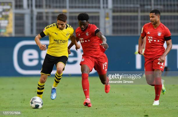 Achraf Hakimi of Borussia Dortmund is challenged by Alphonso Davies and Serge Gnabry of Bayern Muenchen during the Bundesliga match between Borussia...
