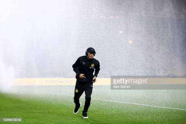 Achraf Hakimi of Borussia Dortmund runs away from the sprinklers prior to the Bundesliga match between Borussia Dortmund and FC Bayern Muenchen at...