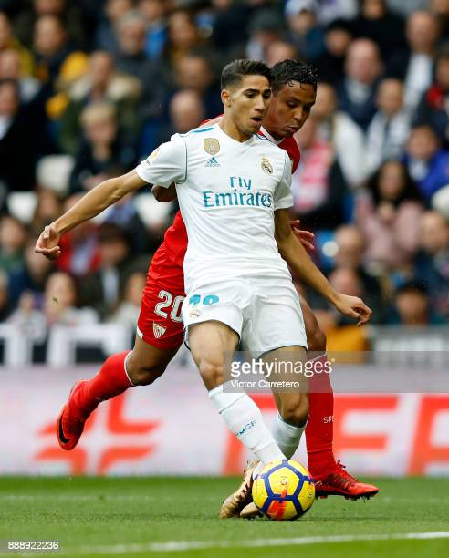 Achraf Hakimi of Real Madrid competes for the ball with Luis Muriel of Sevilla during the La Liga match between Real Madrid and Sevilla at Estadio...