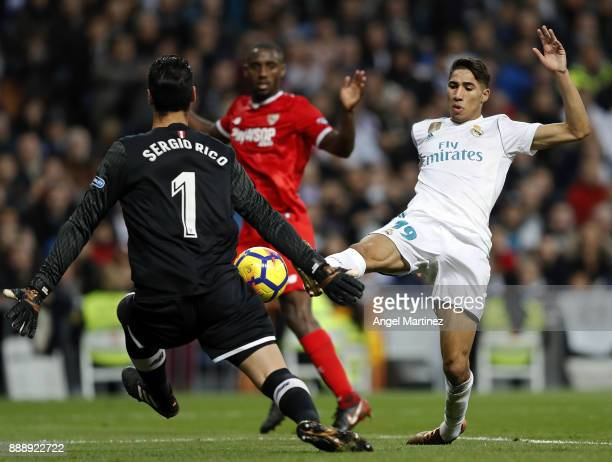 Achraf Hakimi of Real Madrid competes for the ball with Sergio Rico of Sevilla during the La Liga match between Real Madrid and Sevilla at Estadio...