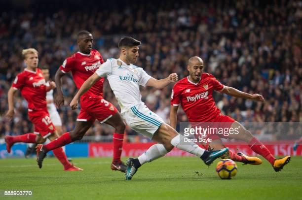 Achraf Hakimi of Real Madrid is tackled by Guido Pizarro of Sevilla during the La Liga match between Real Madrid and Sevilla at Estadio Santiago...