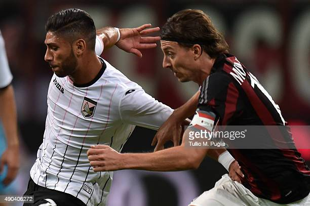 Achraf Lazaar of Palermo and Riccardo Montolivo of Milan compete for the ball during the Serie A match between AC Milan and US Citta di Palermo at...