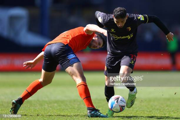 Achraf Lazaar of Watford FC battles for possession with Matty Pearson of Luton Town during the Sky Bet Championship match between Luton Town and...